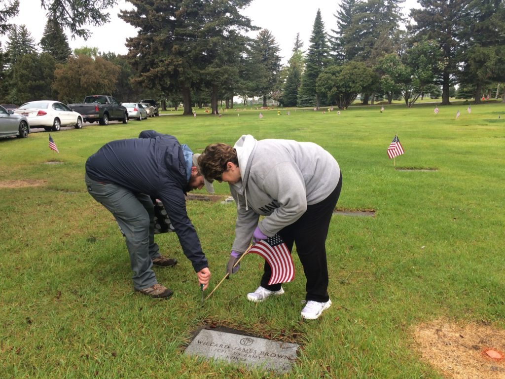Liz Bleaser, Regent of the Fort Hall chapter of the Daughters of the American Revolution, and Liam Kelly, veteran and member American Legion Post 56, place a flag next to the grave of a veteran buried in Fielding Memorial Cemetery | Sydney Jensen, KID NEWSRADIO
